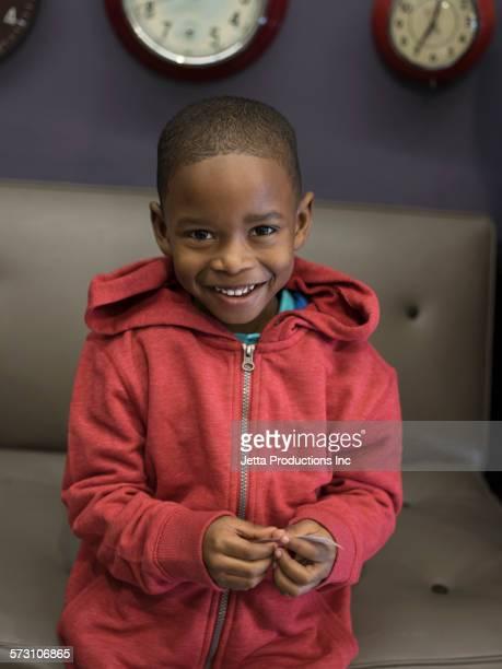 black boy smiling on sofa - casaco - fotografias e filmes do acervo