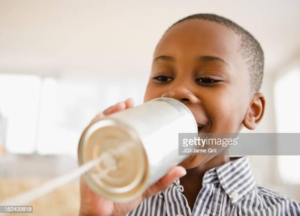 Black boy talking into tin can phone