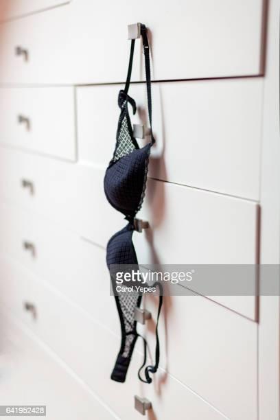 Black  bra hangs from a closet armchair