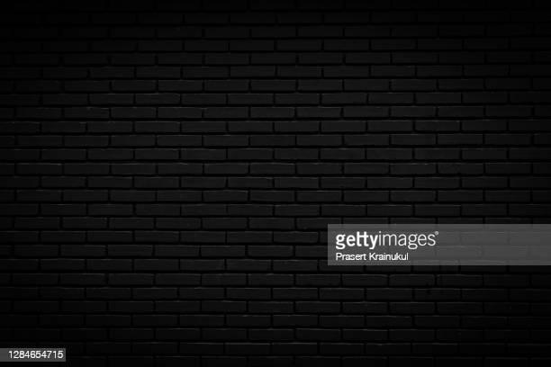 black brick wall. background of empty brick basement wall - colore nero foto e immagini stock