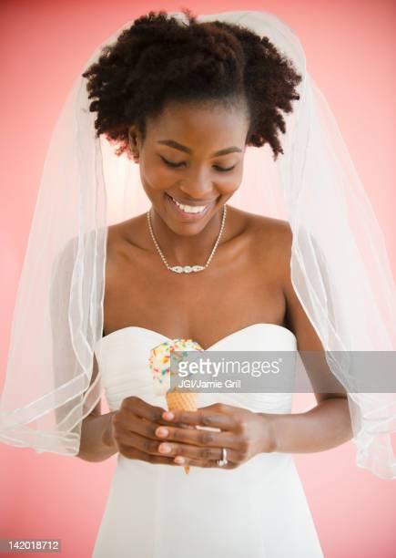 Black bride in wedding dress holding ice cream cone