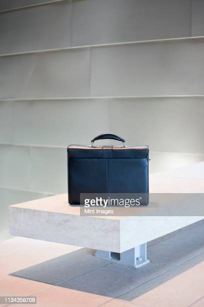 Black Briefcase on White Stone Bench