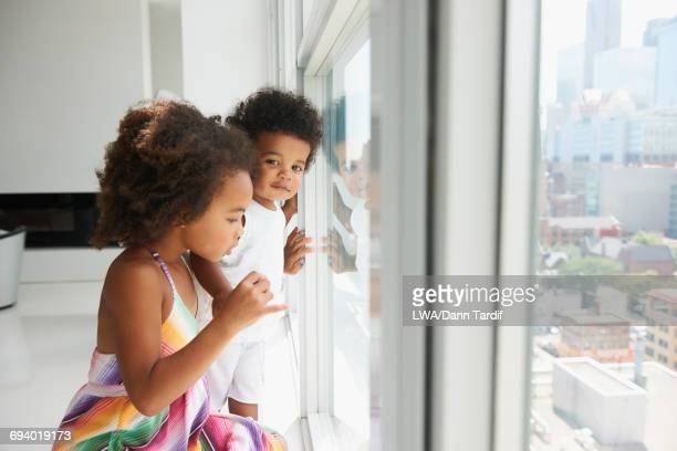 Black brother and sister near window in city