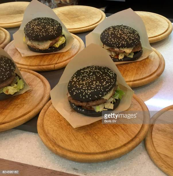 Black burgers with beef on round cutting boards