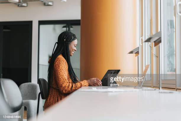black business woman with tablet having video call in the office - wide angle stock pictures, royalty-free photos & images