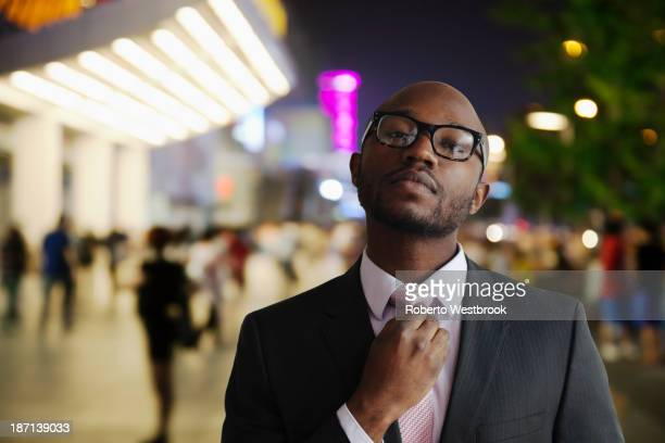 Black businessman adjusting tie on city street