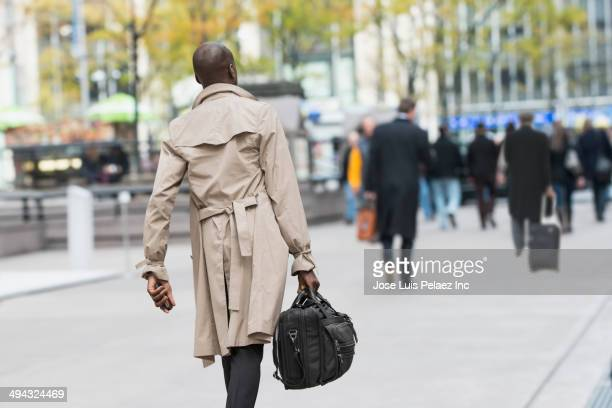 Black businessman carrying bag on city street
