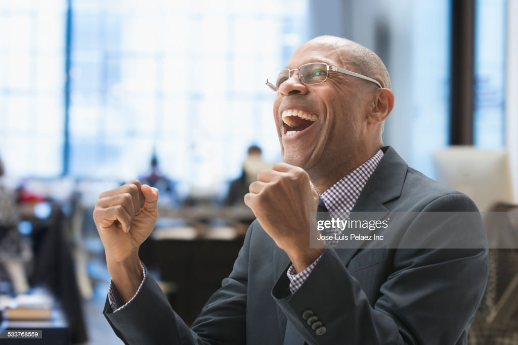 Black businessman cheering in office : Foto stock