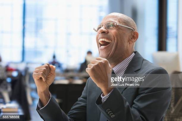 Black businessman cheering in office