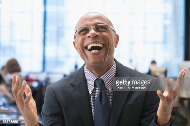 Black businessman cheering in office