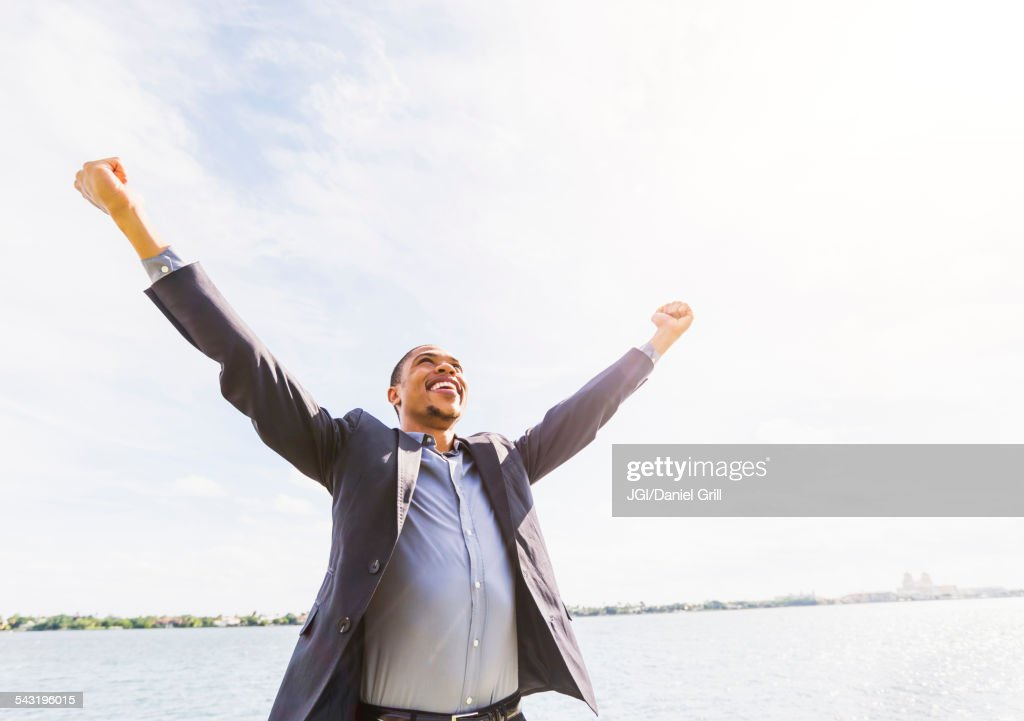 Black businessman cheering with arms outstretched outdoors : Stock Photo