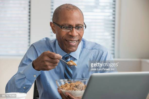 Black businessman eating cereal and working in office