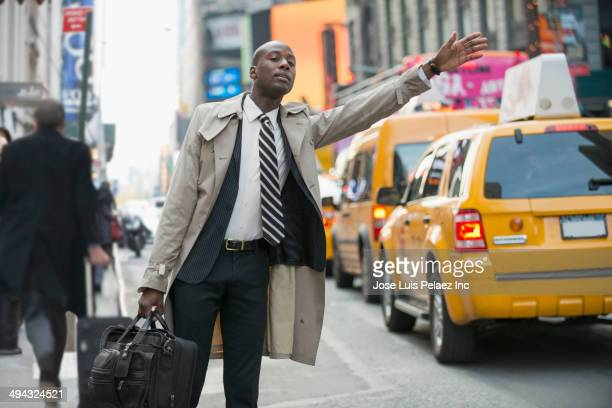 Black businessman hailing taxi on city street