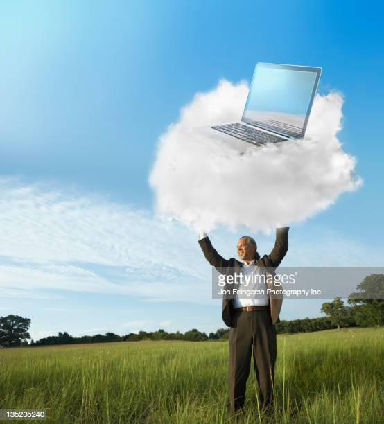Black businessman holding laptop on cloud in field