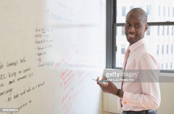 Black businessman holding marker at whiteboard