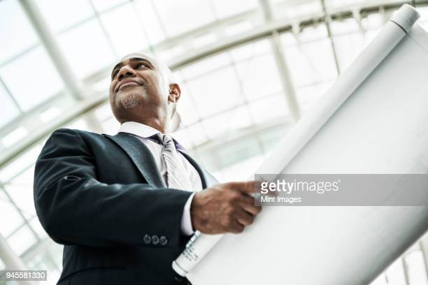 a black businessman holding plans for a new office space in a large glass covered walkway. - unusual angle stock pictures, royalty-free photos & images