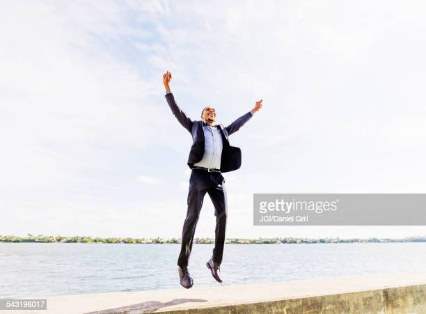 Black businessman jumping for joy outdoors