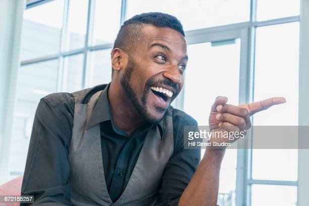 Black businessman laughing and pointing finger