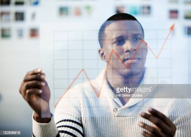 Black businessman looking at line graph