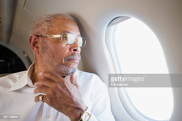 Black businessman looking out airplane window