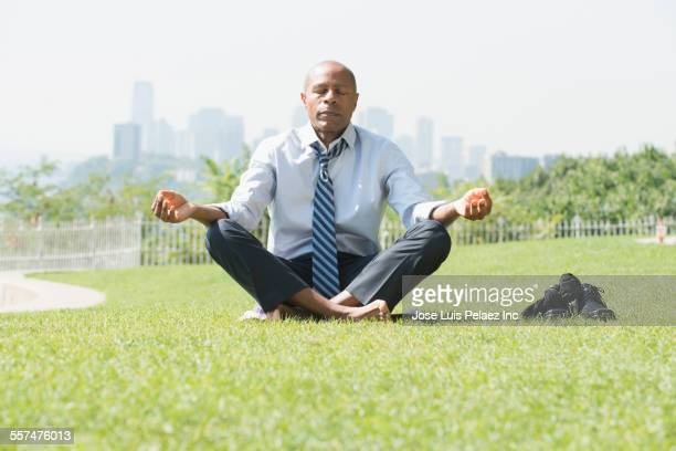 Black businessman meditating on grass