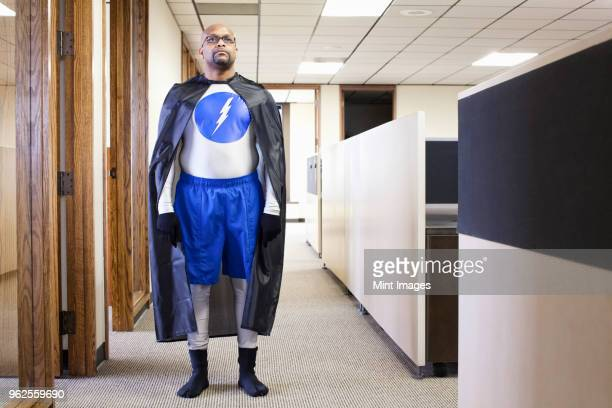 a black businessman office super hero standing in an office hallway. - superhero stock pictures, royalty-free photos & images