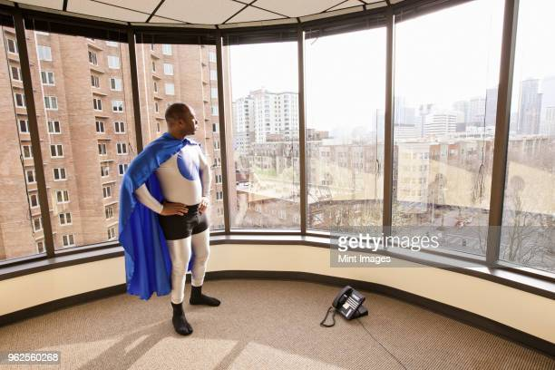 A black businessman office super hero stands at an office window and ponders his next business move.