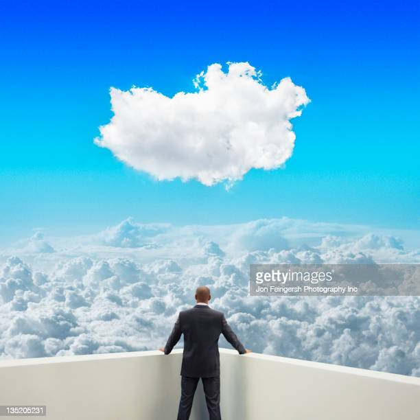 Black businessman on balcony looking at clouds