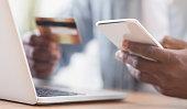 Black businessman paying his bills online using app in smartphone