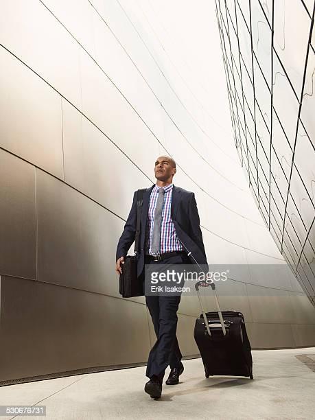 Black businessman rolling luggage