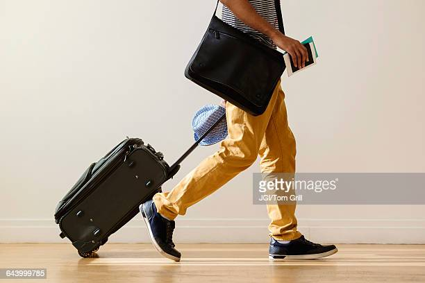 Black businessman rolling luggage