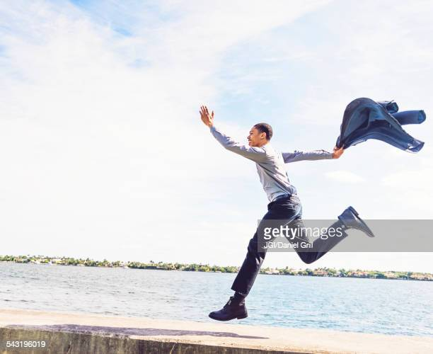 Black businessman running on waterfront wall outdoors