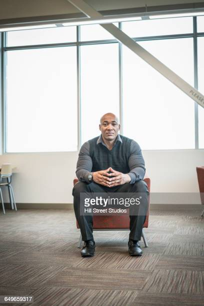 black businessman sitting in office lounge - tensed idaho stock photos and pictures