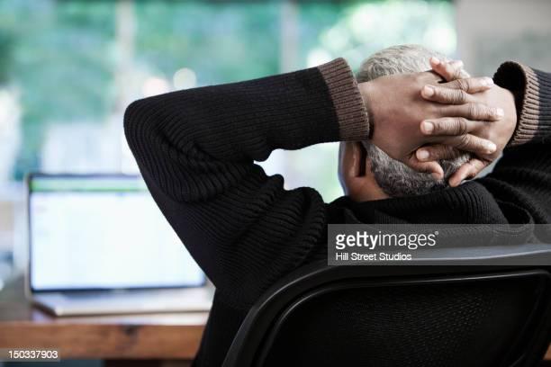 Black businessman sitting with hands behind head