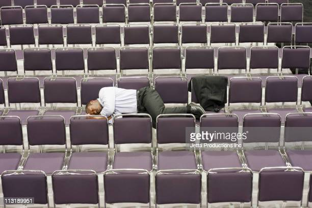 Black businessman sleeping in empty conference center
