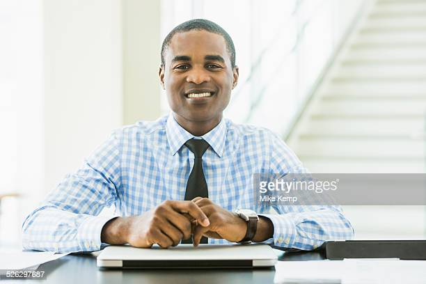 black businessman smiling at desk in office - multiculturalism stock pictures, royalty-free photos & images
