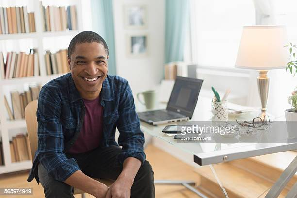 black businessman smiling at desk - one mid adult man only stock pictures, royalty-free photos & images