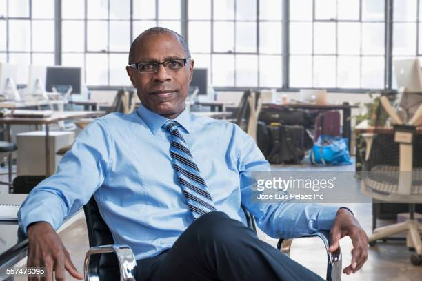 Black businessman smiling in empty office