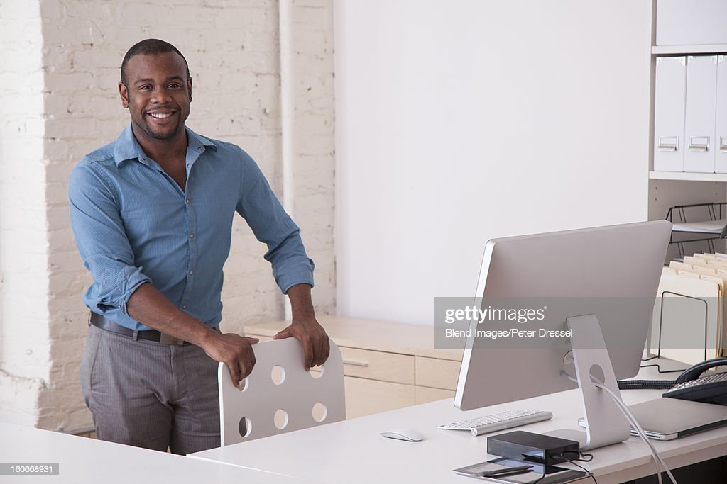 Black businessman standing at desk in office : Stock Photo
