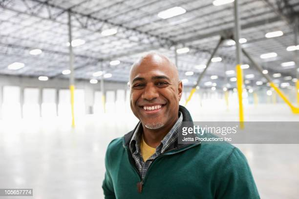 Black businessman standing in empty warehouse