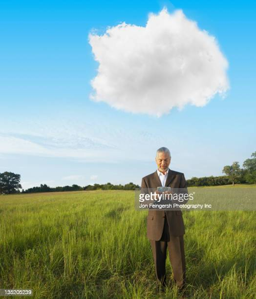Black businessman standing in field text messaging on cell phone