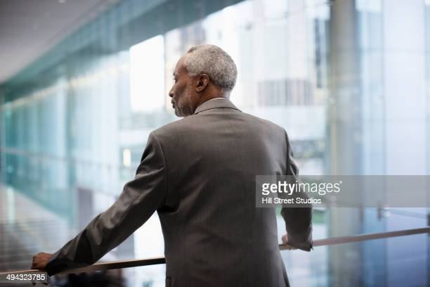 Black businessman standing on balcony in office