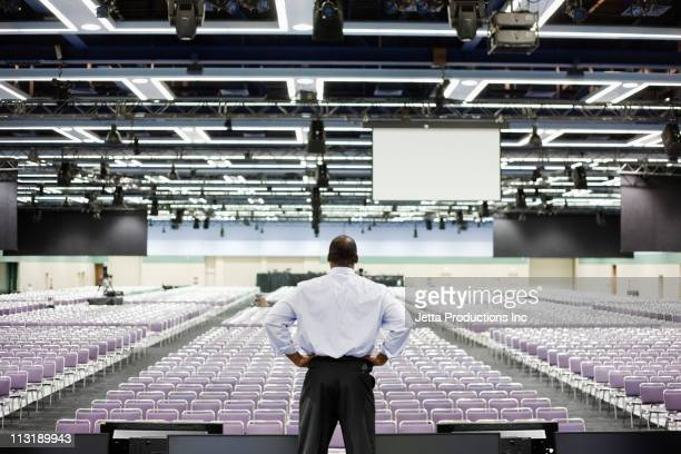 black businessman standing on stage in empty conference center - conferenza di lavoro foto e immagini stock