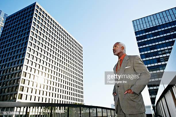 Black businessman standing on urban walkway