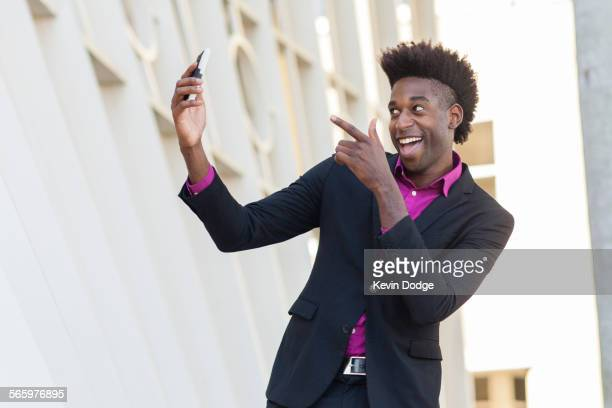 black businessman taking selfie outside building - tenue soignée photos et images de collection