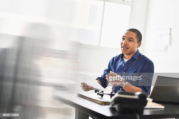 Black businessman talking at office desk