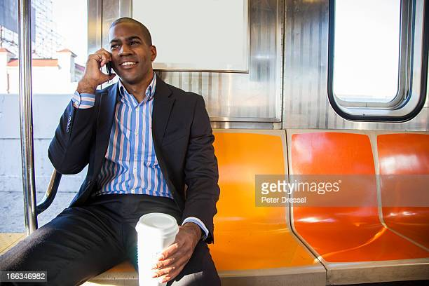 Black businessman talking on cell phone and riding commuter train