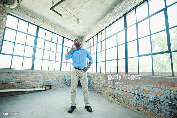 black businessman talking on cell phone in warehouse - 商業不動産 ストックフォトと画像