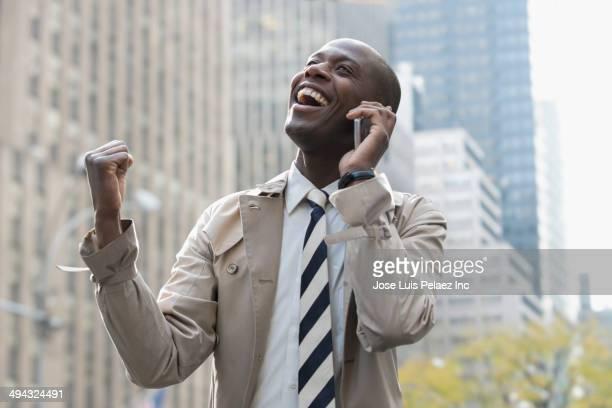 black businessman talking on cell phone on city street - トレンチコート ストックフォトと画像