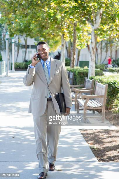Black businessman talking on cell phone outdoors